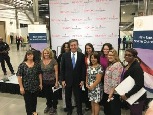 Governor Roy Cooper stands with Revlon employees.