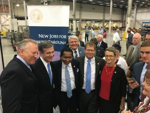 Bill Welz of Revlon stands with Governor Roy Cooper, Senator Floyd McKissick Jr., Granville County Chairman Tim Karan, and Oxford Mayor Jackie Sergent.
