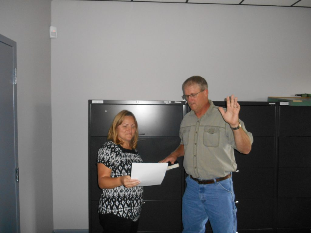 Jessie Fields of Granville County Soil and Water District administers the oath of office to Dean Askew.