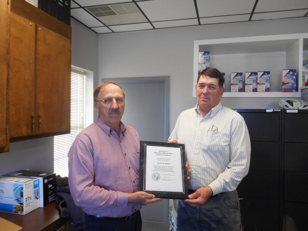 Randy Guthrie, Vice Chair of the Granville Soil and Water District Board, was recognized for 10 years of service at the district's recent meeting by District Chair, Ronnie Burnette. Guthrie, retired from the Bull Research Station in Butner, is still active on his farm, raising beef cows and in forestry.