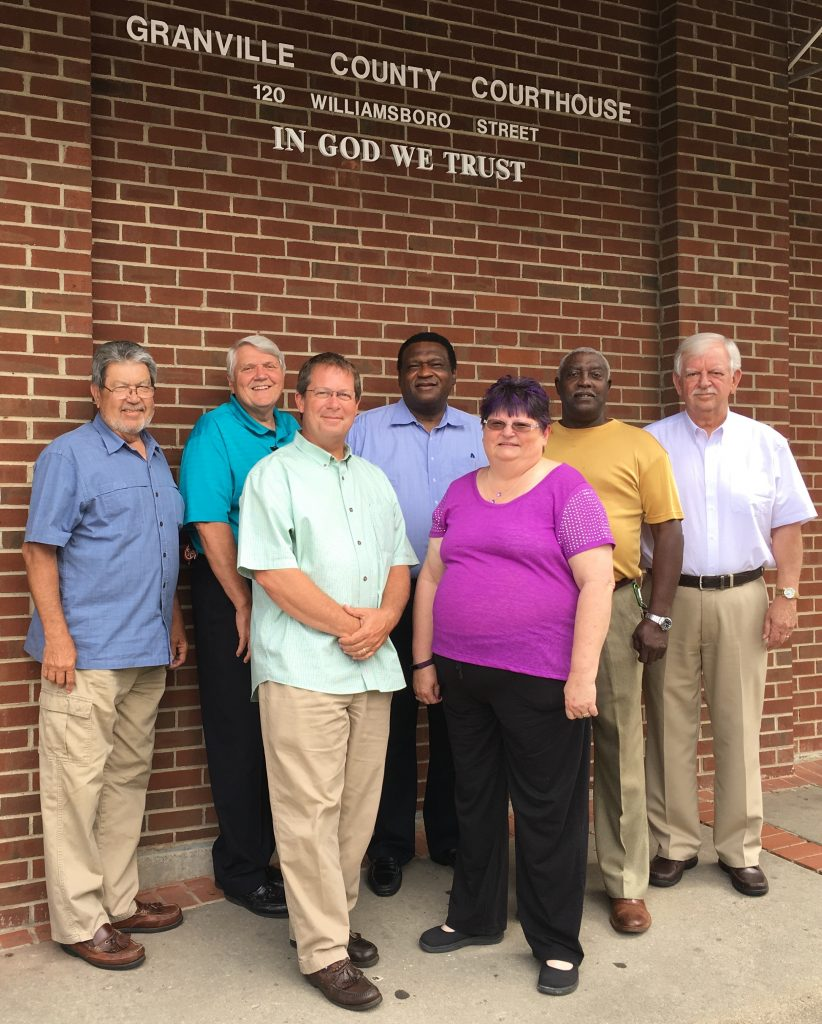 """Granville County Commissioners stand next to the """"In God We Trust"""" sign at the Granville County Courthouse."""