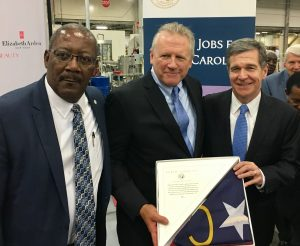 Granville County Economic Development Director, Harry Mills (pictured left), stands with Revlon Senior Vice President of Manufacturing (America's), Bill Welz, and Governor Roy Cooper at today's announcement of the addition of 55 new jobs at the Revlon Oxford plant
